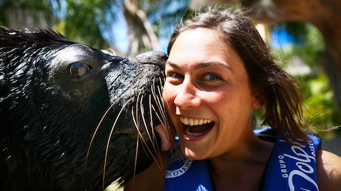 Girl getting a kiss on the cheek from a sea lion at Aquaventuras Park