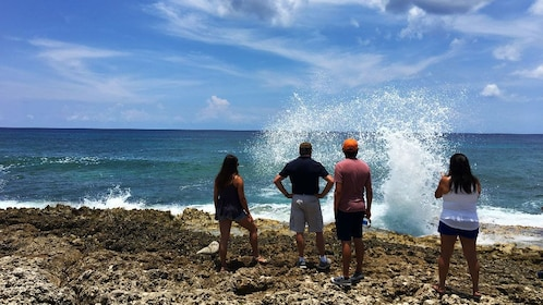 Group watches water crash among rocks in Cayman Islands