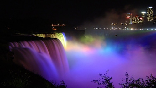 Niagara Falls lit up with different colored lights at night.