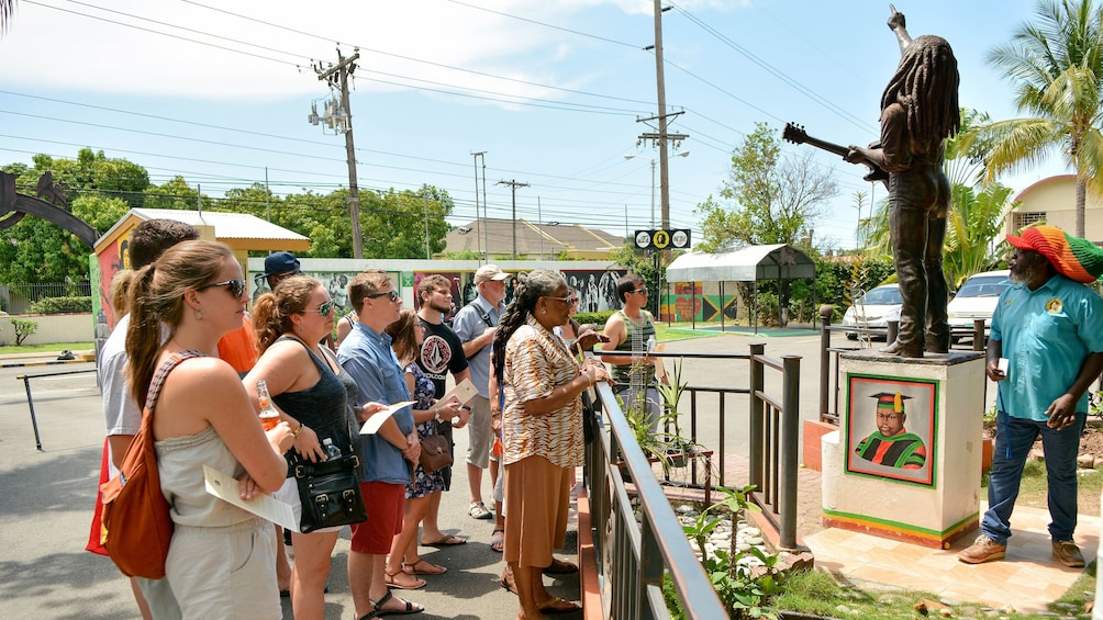 Show item 2 of 10. Tour group looking at a Bob Marley statue in Kingston