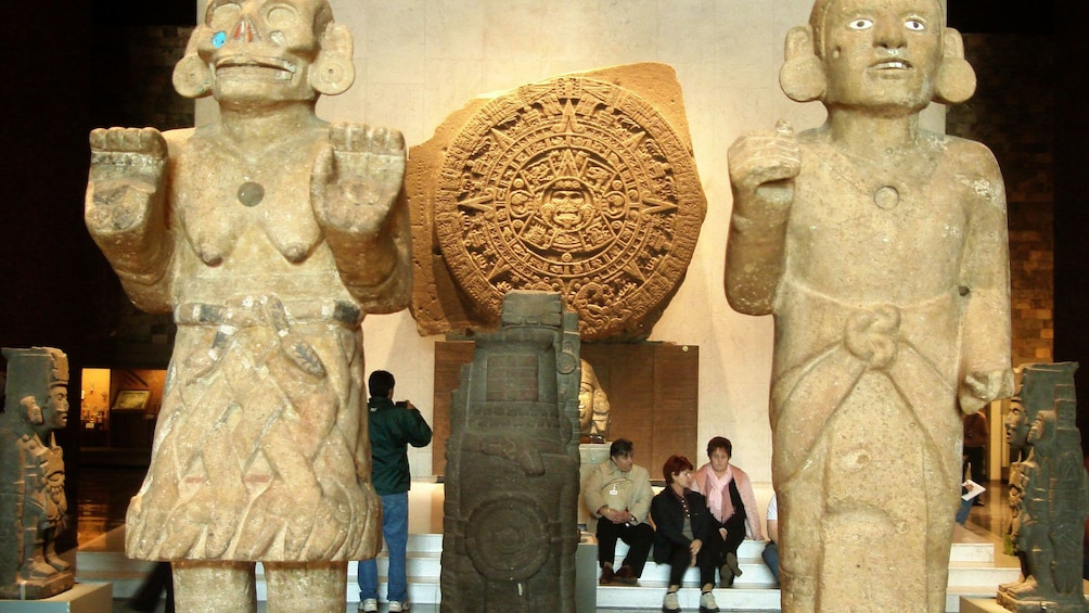 Large human statues with mayan stone carving in background in anthropology museum in Mexico City