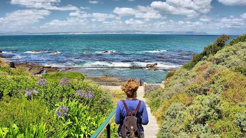 woman walking down foot path of Walker Bay in Hermanus
