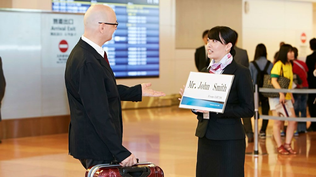 Show item 1 of 4. Airserve employee holding sign for client in airport in Tokyo