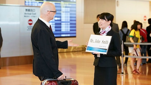 Airserve employee holding sign for client in airport in Tokyo