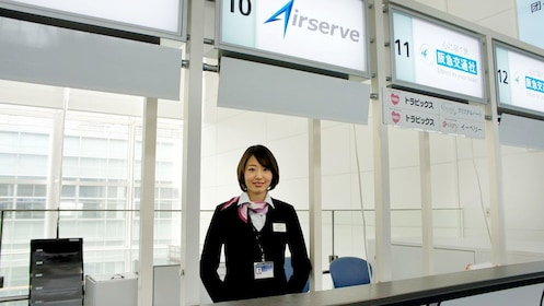 Airserve employee waiting behind counter of business in Tokyo