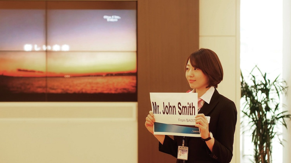 Show item 1 of 5. Airserve employee holding sign, waiting for client in airport in Tokyo