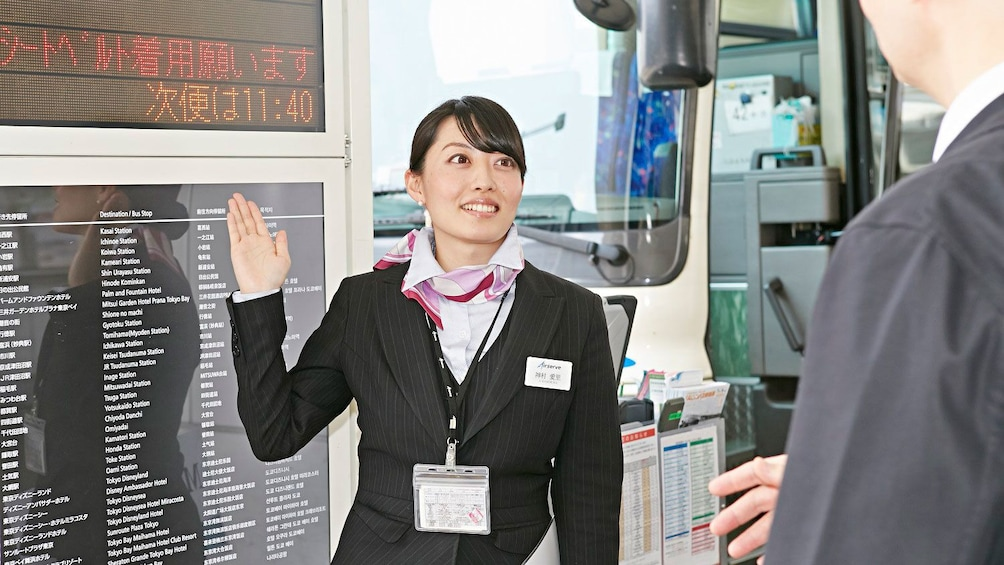 Show item 3 of 5. Airserve employee directing client outside of airport in Tokyo