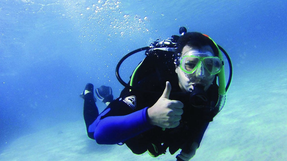 Show item 2 of 8. Scuba diver giving thumbs up while diving around Moreton Island