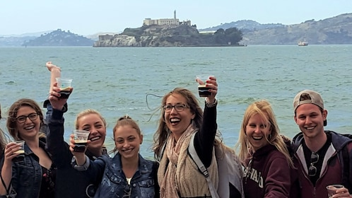Group toasting with glasses of beer and Alcatraz in the background in San Francisco