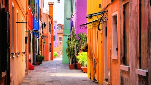 Sidewalk flanked by colorful buildings in Burano