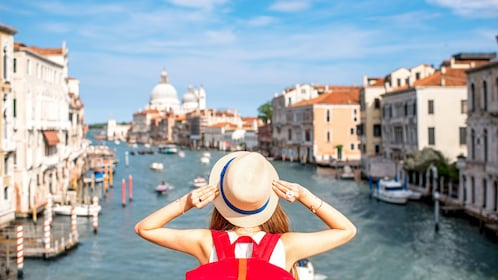 Tourist holding hat as she overlooks canal in Venice