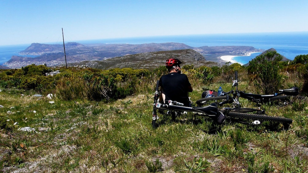 Apri foto 2 di 5. Mountain biker taking break on mountain looking over wide view on Table Mountain