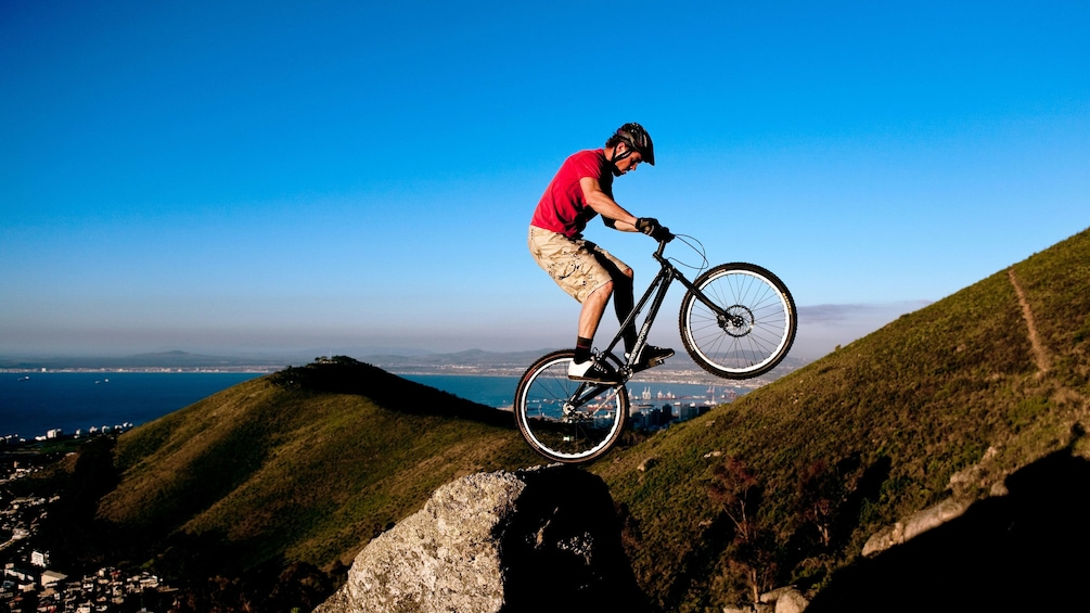 Apri foto 3 di 5. Mountain Biker balance bike on rock on Table Mountain