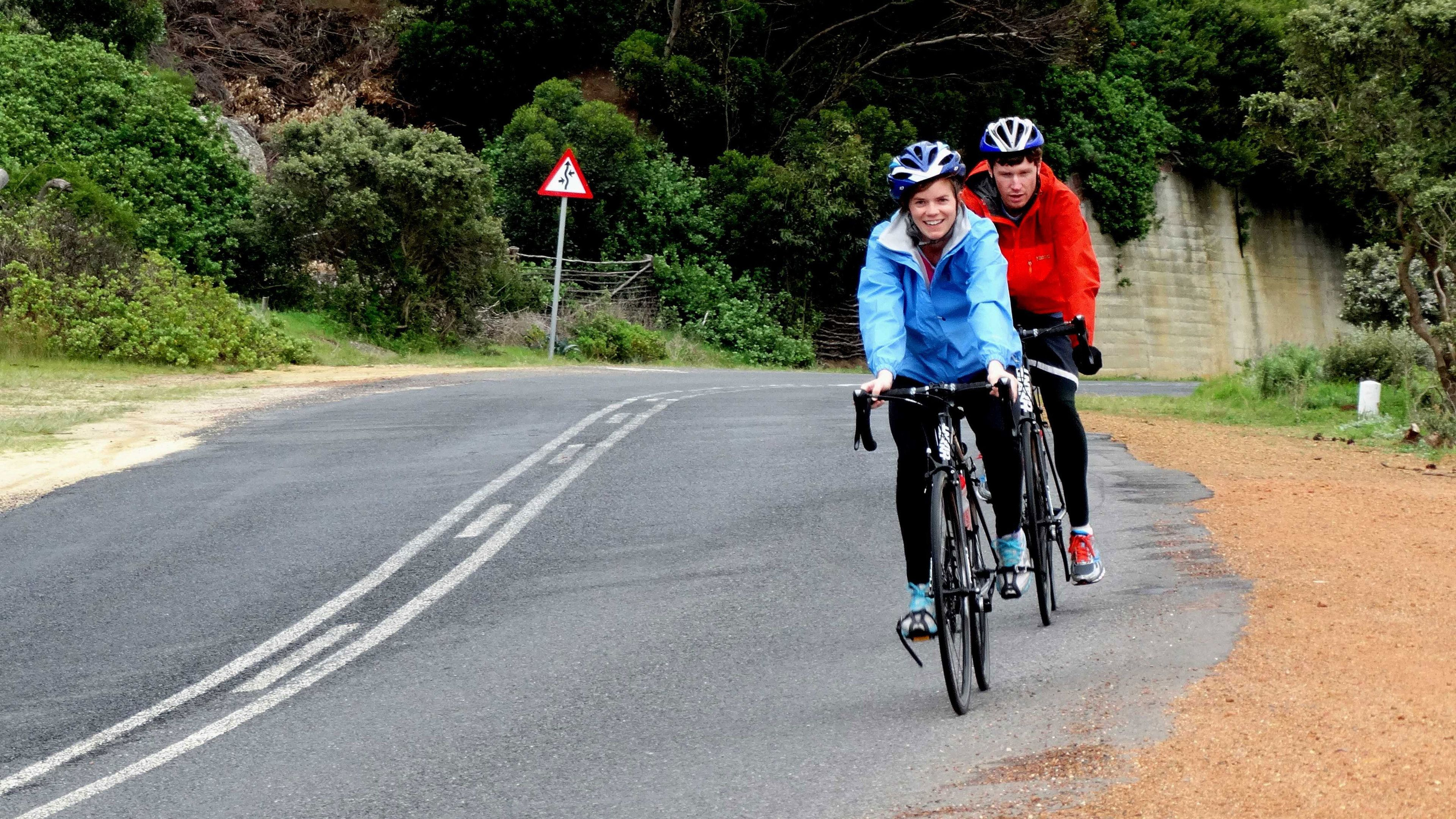 Two people on bikes down a country road