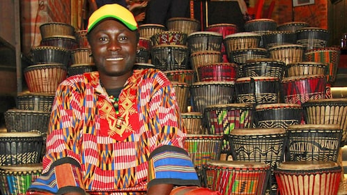Man sits next to woven baskets
