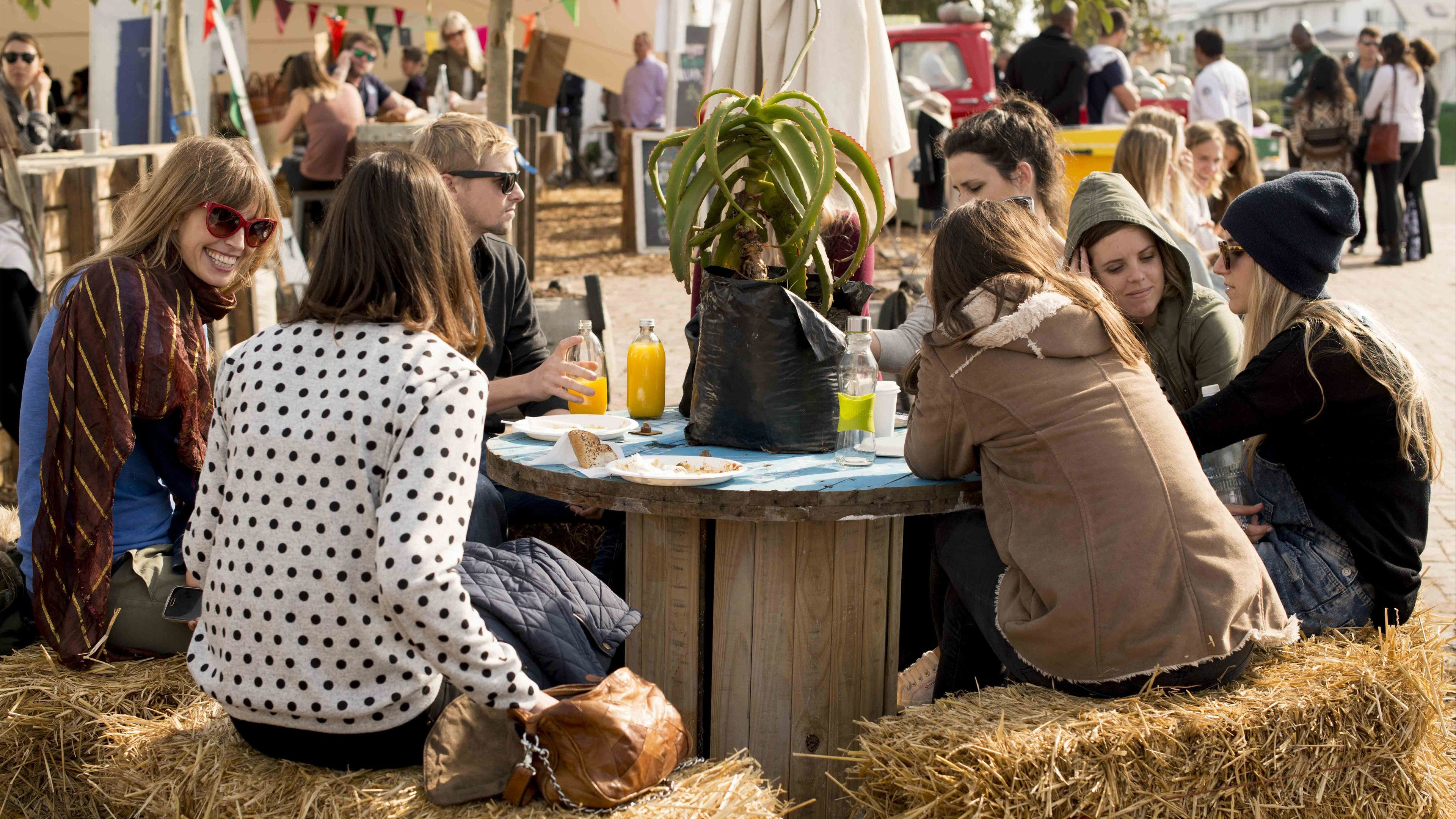 Group eating at a table with haystack benches at a market in Cape Town