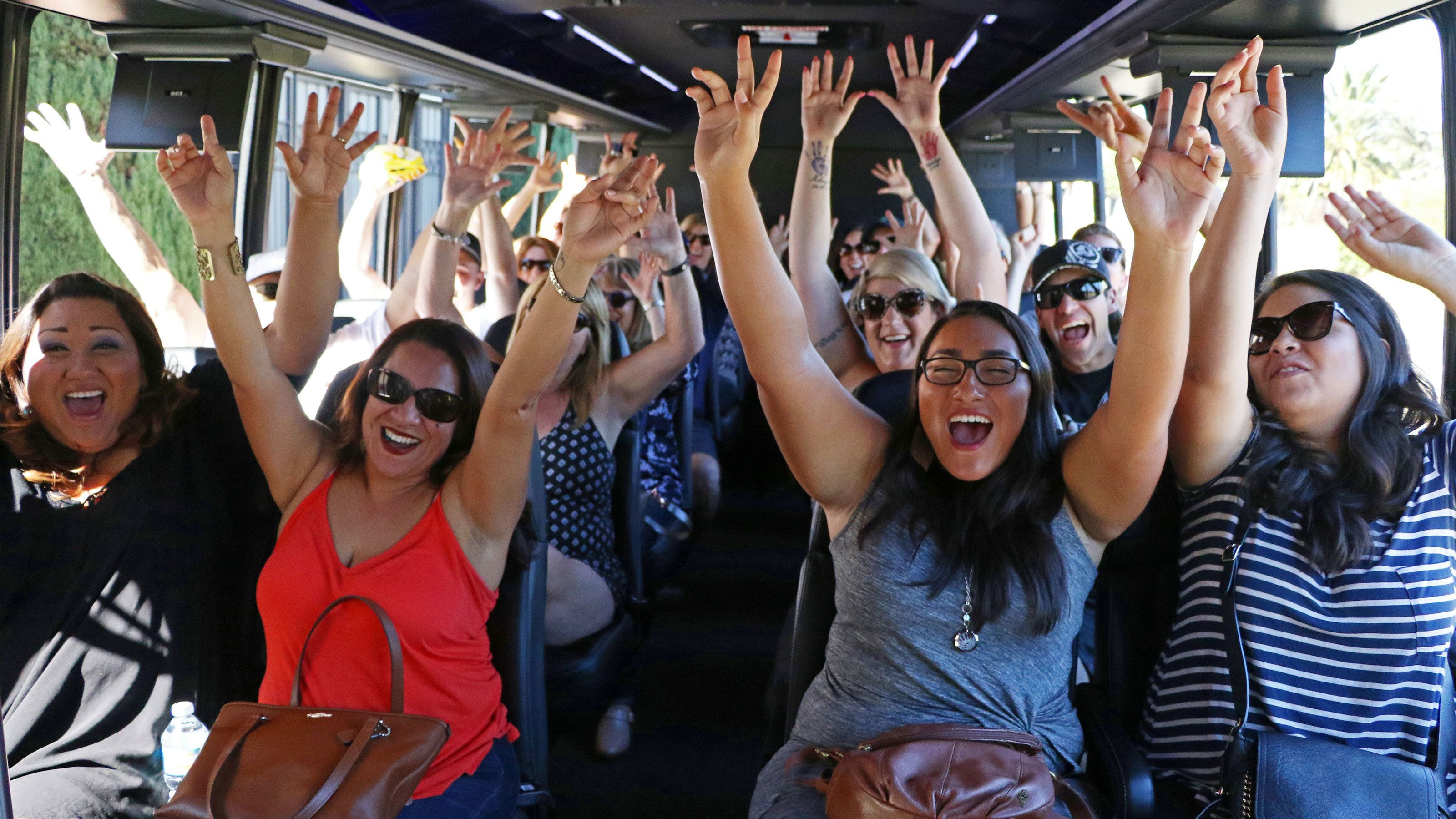 Tourist raising hands and cheering on tour in Los Angeles