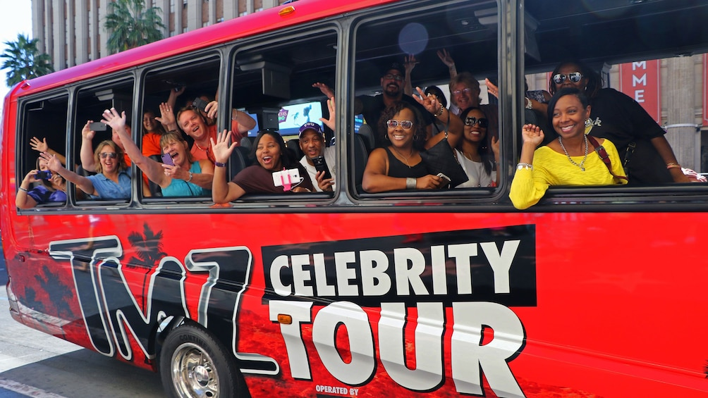 Show item 1 of 6. Tourist looking out the bus and taking pictures on the TMZ Celebrity Tour in Los Angeles