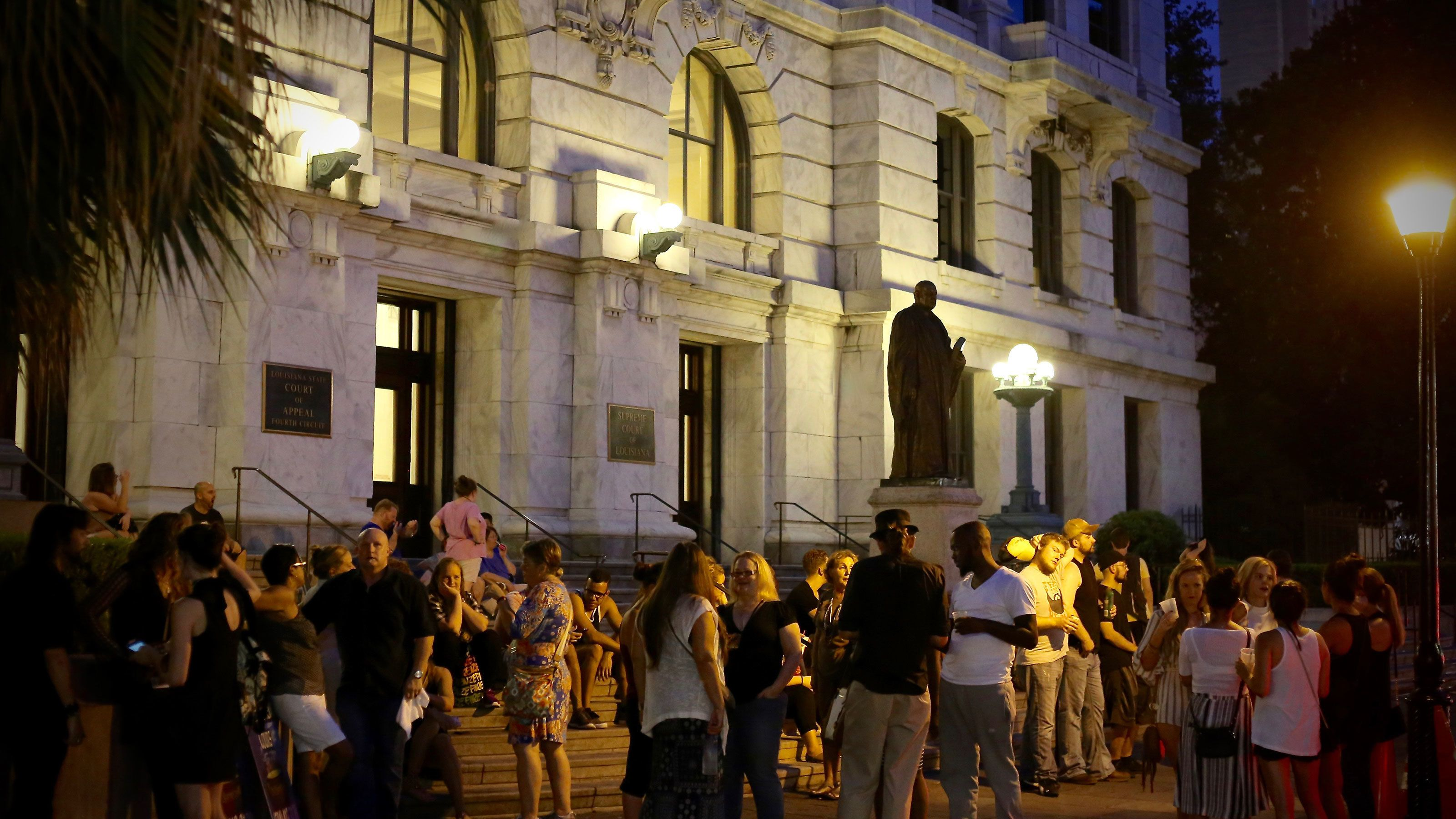 Tourist waiting outside building at night for tour to start in New Orleans
