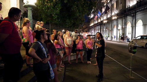 Tour guide talking to tourists at night in New Orleans