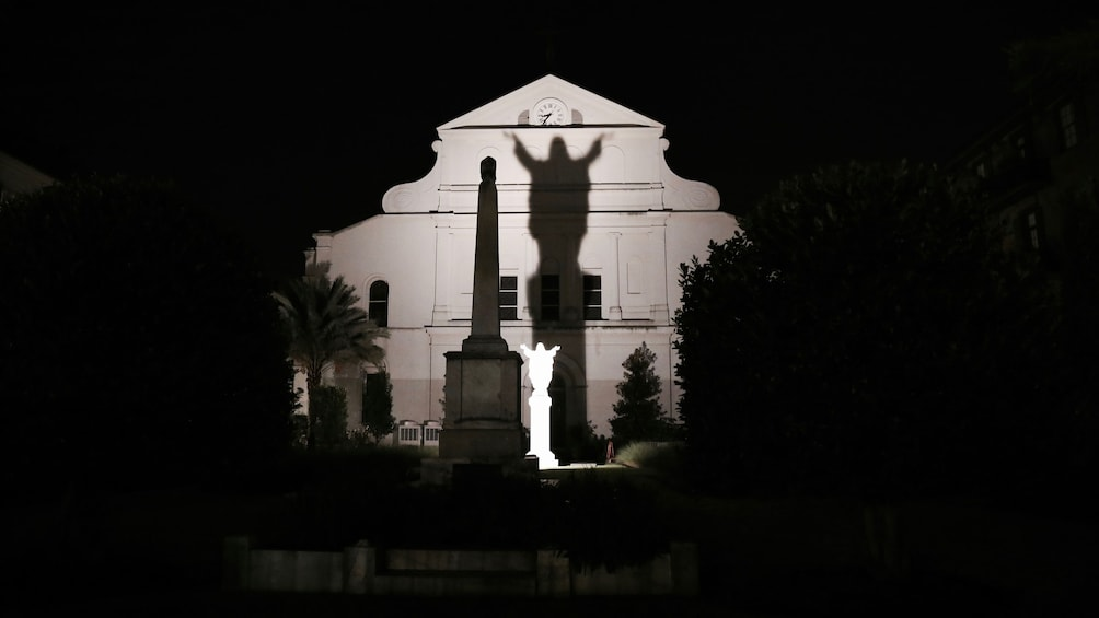 Show item 2 of 11. Shadow of statue casted upon building in New Orleans