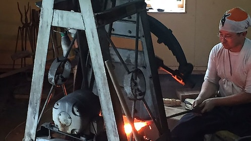 Blacksmith working on glowing hot piece of metal in Kyoto