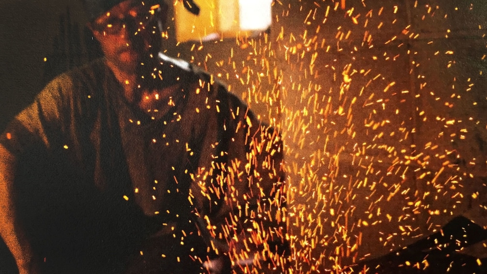 Show item 2 of 5. Embers fly as work is done on metal with the blacksmith in the background in Kyoto