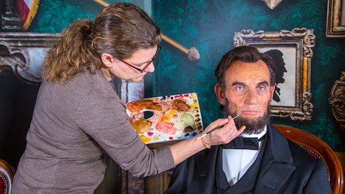Wax figure of Abraham Lincoln being touched up by artist at Madame Tussauds in Orlando
