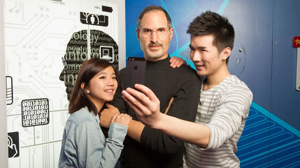 Wax figure of Steve Jobs with people taking a selfie at Madame Tussauds in Orlando.