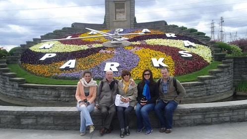 Family sits by Niagara Parks sign near Niagara Falls