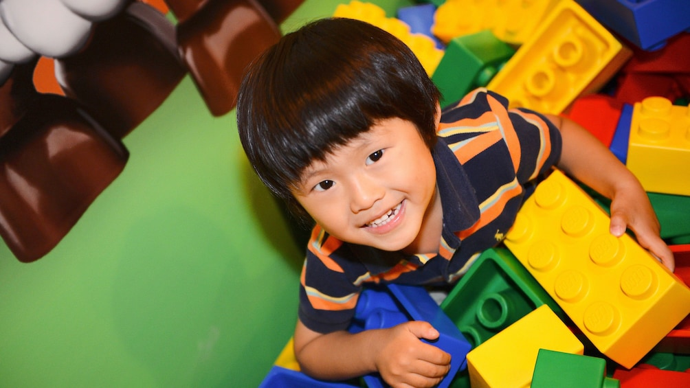 Small boy playing with large legos in Legoland in Tokyo