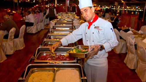 Chef placing food out onboard the Rustar Floating Restaurant in Dubai