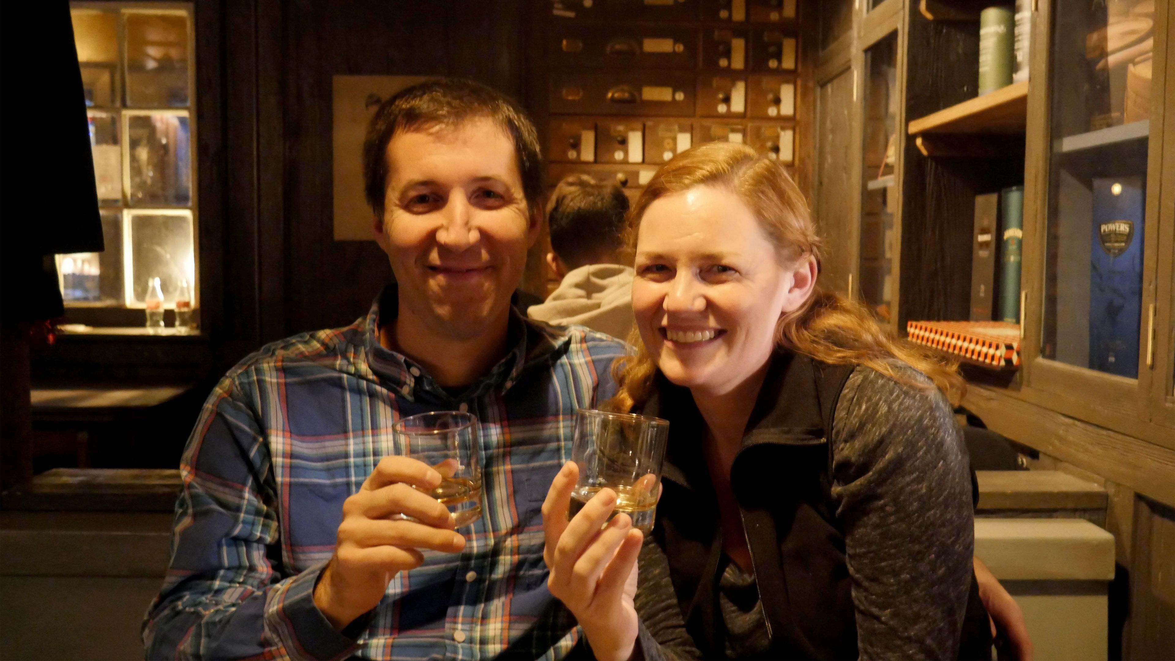 Couple with glasses of whiskey at a bar in Dublin