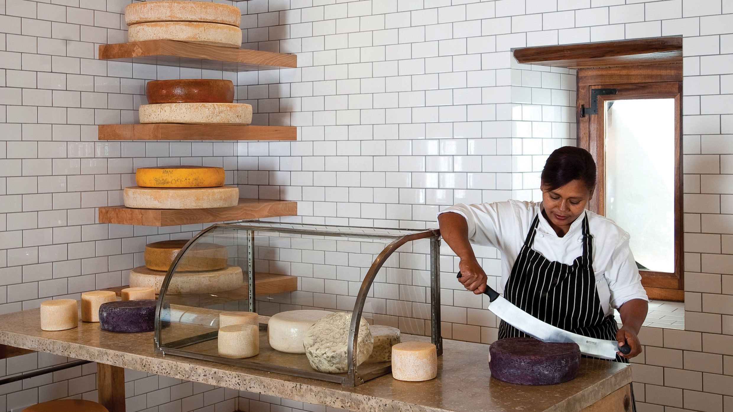 Winery staff slicing wheels of cheese in Cape Town