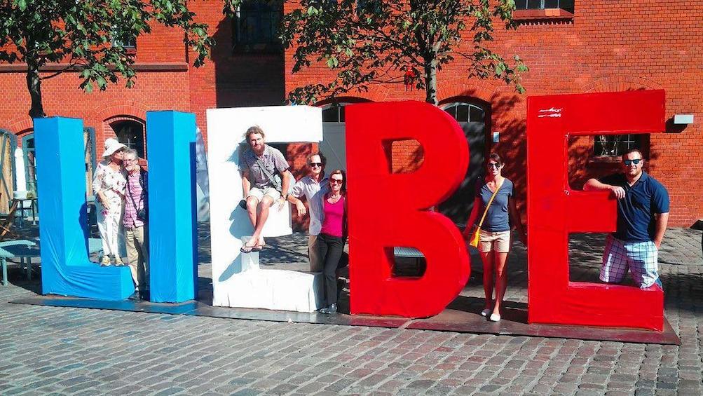 Åpne bilde 3 av 5. People hanging on a Liebe sculpture