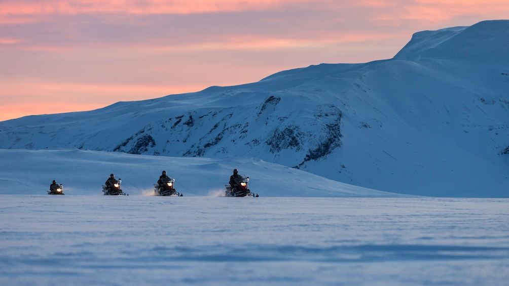Show item 4 of 10. Snowmobilers in the mountains