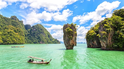 Boat passes by rock formation in the water of Krabi