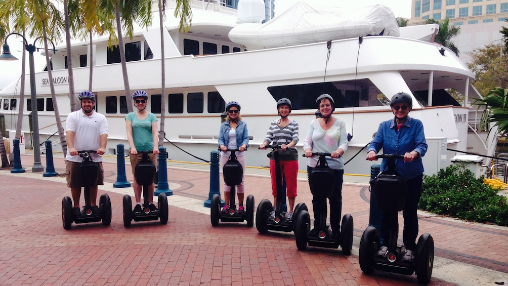 Show item 1 of 5. Tourists on segways have picture taken in front of yacht in Fort Lauderdale