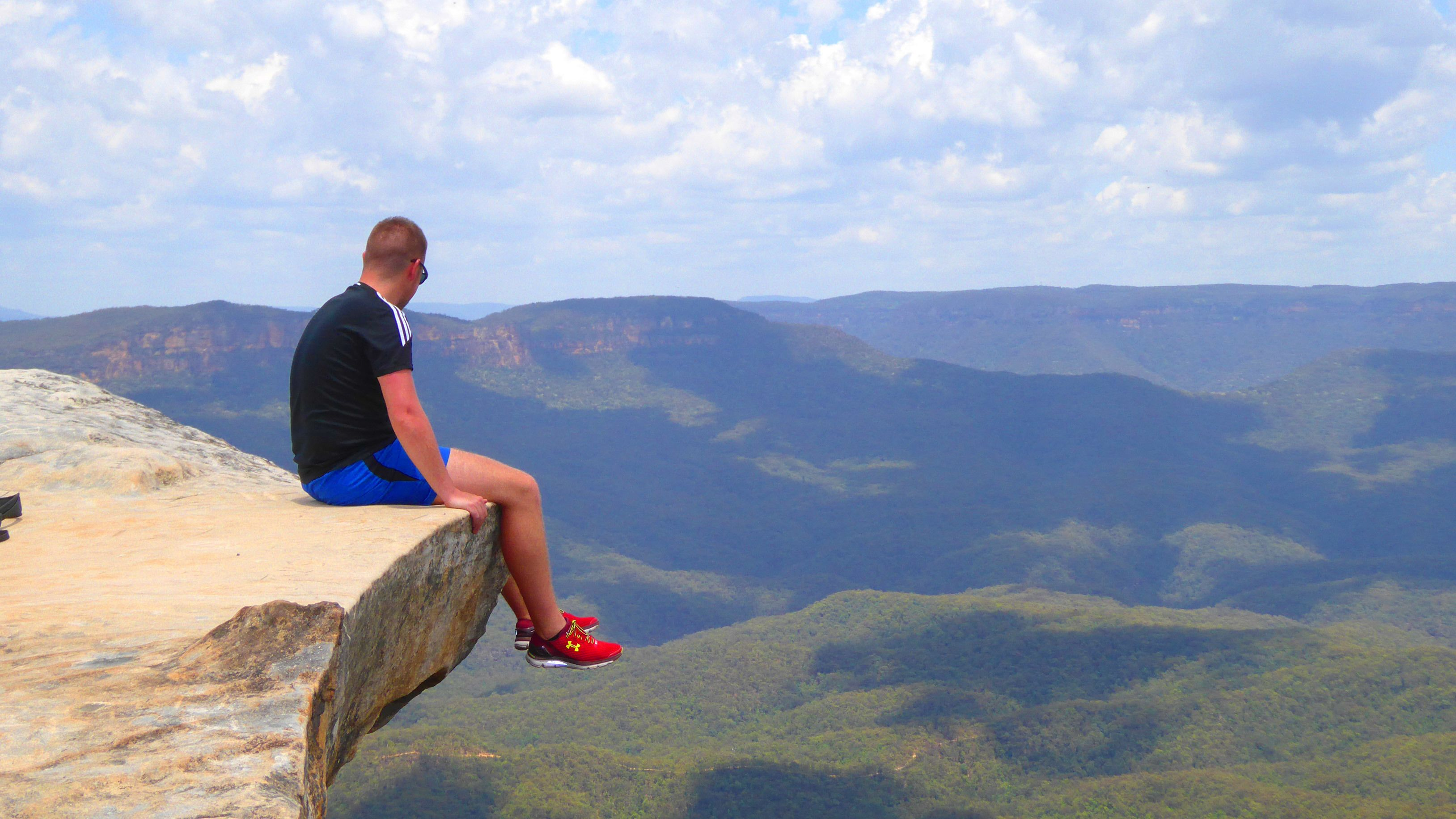 Man hanging feet over a cliff in Australia