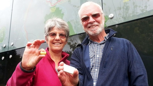 Older couple holding small pieces of gold in Waikato