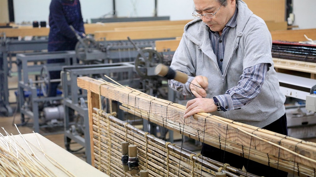 Show item 4 of 5. View of a man on the Kyoto style Kasumi Bamboo Mat Making tour