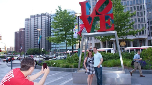 Tour guide takes picture of tourists standing underneath LOVE artwork in Philadelphia