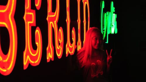Woman giving peace sign next to neon lights at night in Warsaw