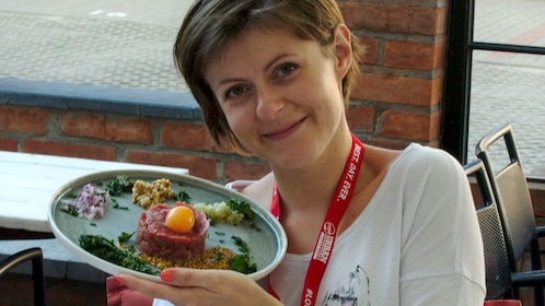 Woman holding up a plate of food at a restaurant in Warsaw