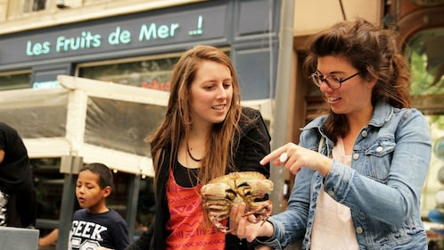 Two women looking at crab in farmers market in Marseille