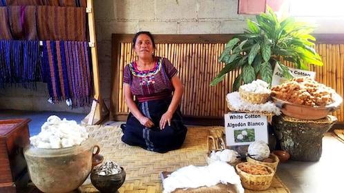 Woman sits with various materials for weaving in Cerro de la Cruz