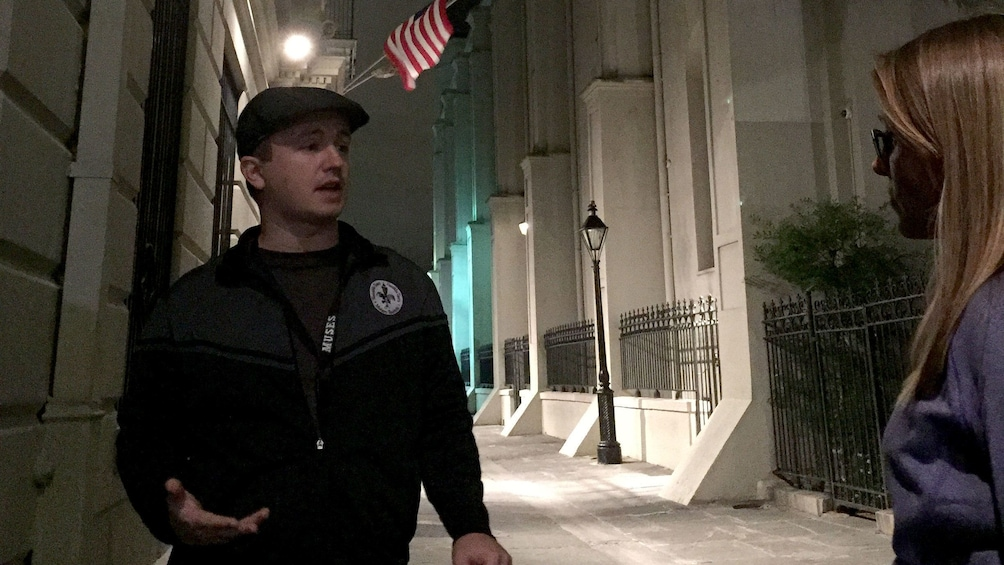 Show item 3 of 5. Tour guide describing sites to a woman at night in New Orleans