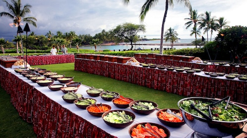 Rows of tables with different plates of food in a hawaiian luau