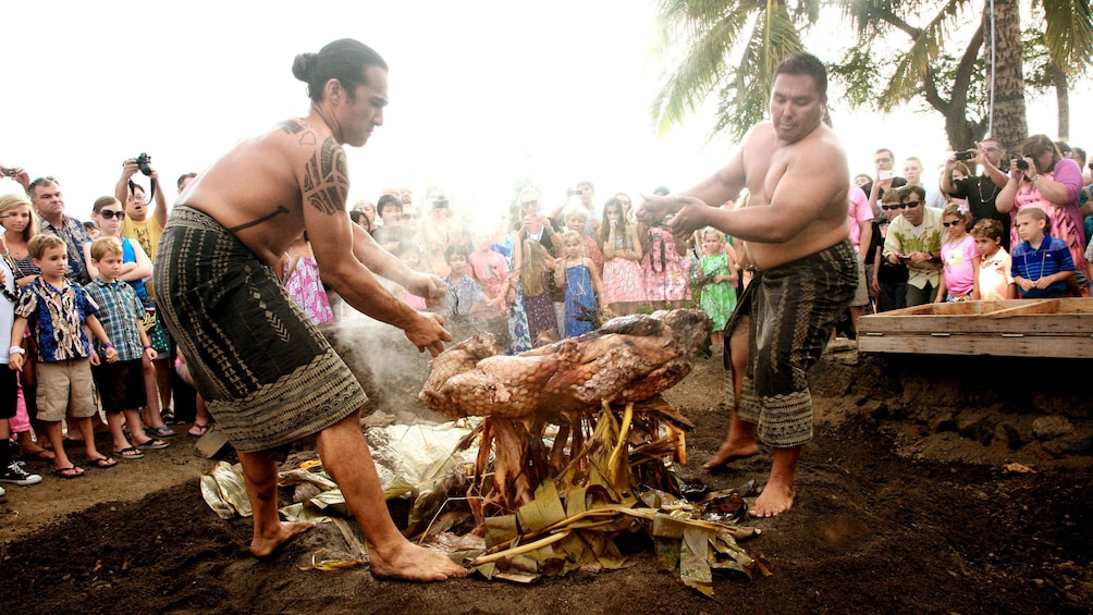 Show item 2 of 8. Two hawaiian men roasting a pig over a fire in Hawaii