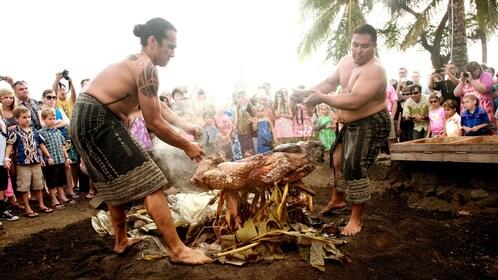 Two hawaiian men roasting a pig over a fire in Hawaii